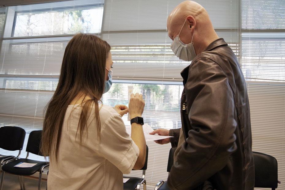 Директор Центра развития донорства костного мозга Любовь Белозерова объясняет добровольцу, как пользоваться палочками для взятия пробы