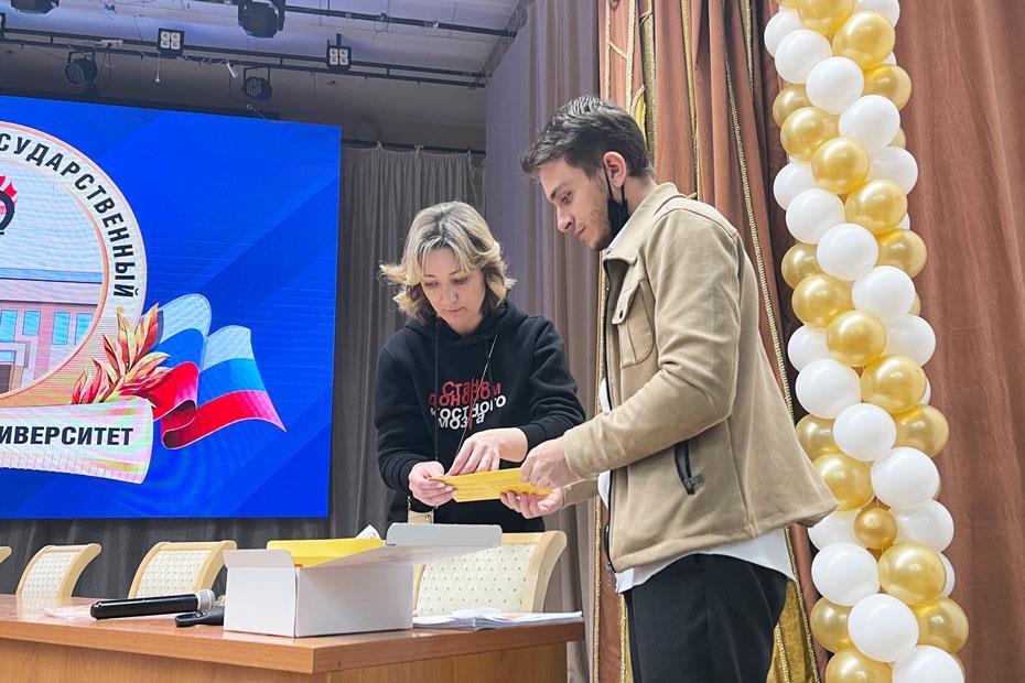 Адам Мякиев передает конверт с набором и документами Екатерине Кузнецовой