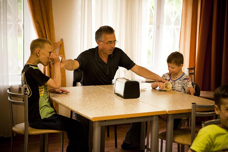 4. Волонтер Сергей Лебедев помогает Мише и Дане за обедом. Едят они пока, честно говоря, ужасно неаккуратно, но чего можно ждать от детей, которых несколько лет кормили только жидкой пищей…
